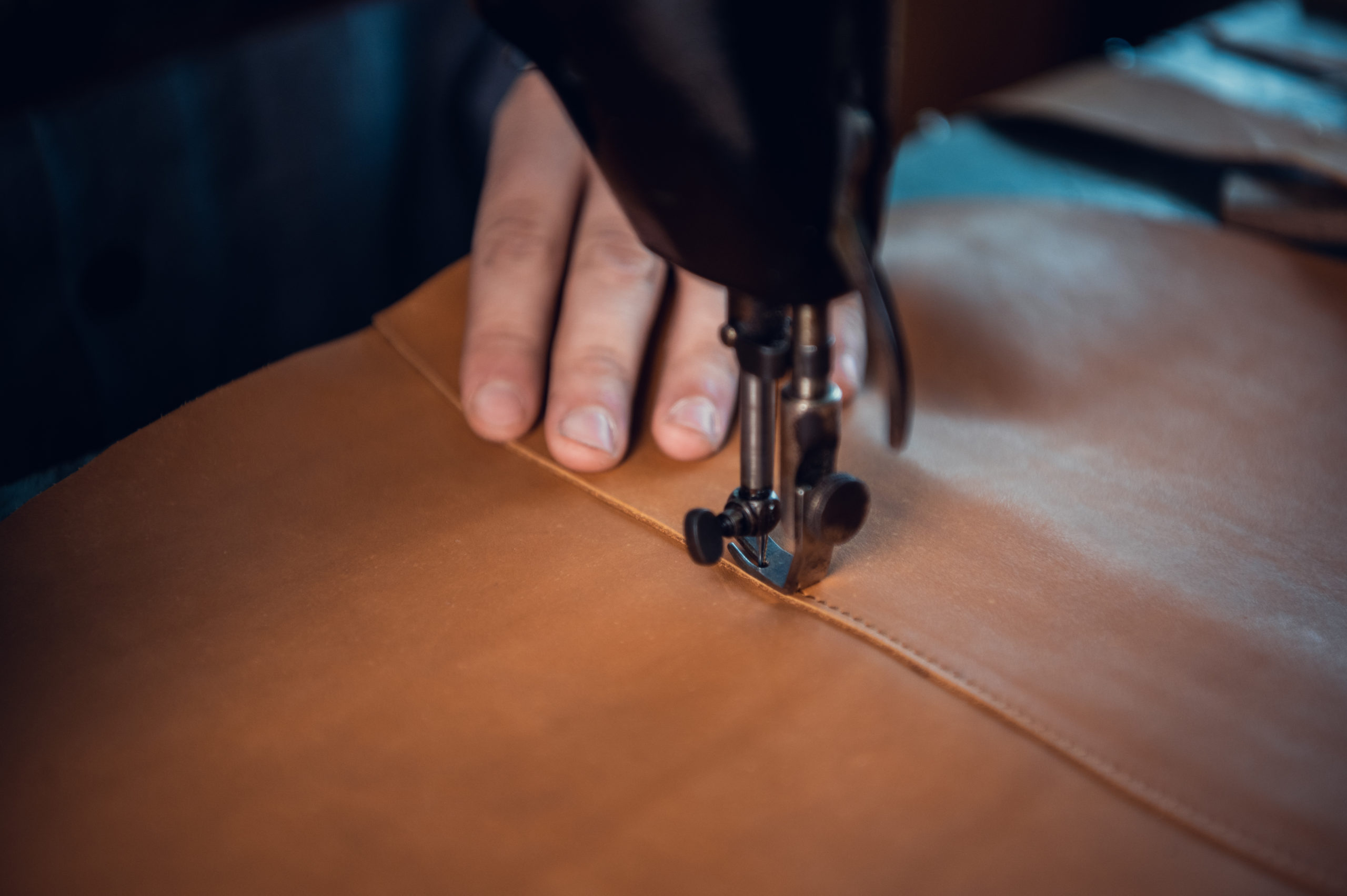 The process of stitching two pieces of genuine leather by a shoemaker on a special old-school sewing machine. Stitches of thread and the hand of the master